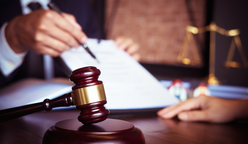Image of man with document in background and gavel in foreground