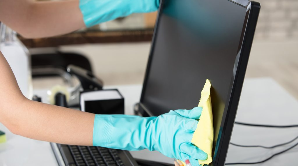 Woman with gloved hands cleaning a workplace desk